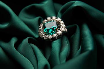 Zielony szmaragdowy pierścionek zaręczynowy moda diament na zielonym tle satyny. Luksusowa biżuteria damska, zbliżenie. Selektywne skupienie