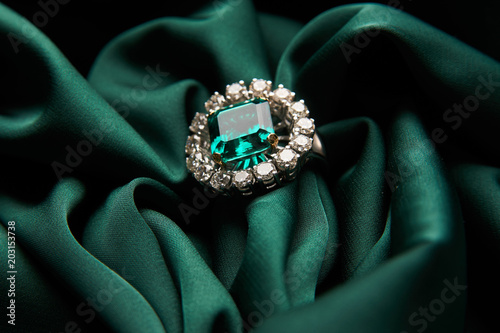 Fotografía Green emerald fashion engagement diamond ring on green satin background