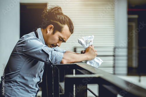 Foto  Asian man crushing paper because strain from his work.