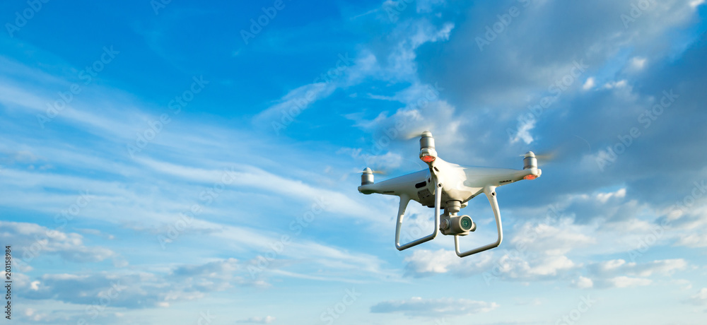 Drone flying overhead in cloudy blue sky