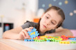 canvas print picture - Little girl with autistic disorder playing at home, closeup of puzzles