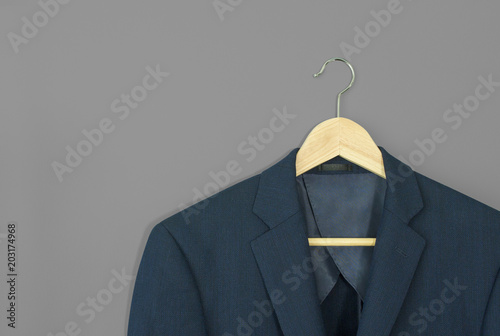 Fotografiet wood hanger with navy blue suit isolated on grey background
