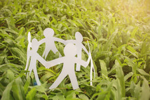 Closeup White Paper Cut People In A Circle Over Green Grass Background. Teamwork Business Meeting Friendship Communication Together World Peace Concept