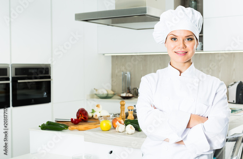 Portrait of the woman proffesional who is posing with devices in the kitchen