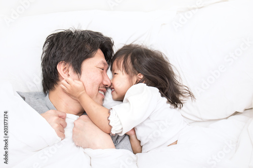Father and daughter laughing and bonding in bed. Daddy and his little girl spending time at home. Fun love family lifestyle concept.