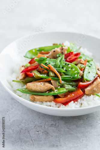 Photo  stir fry chicken and vegetables with rice in white bowl