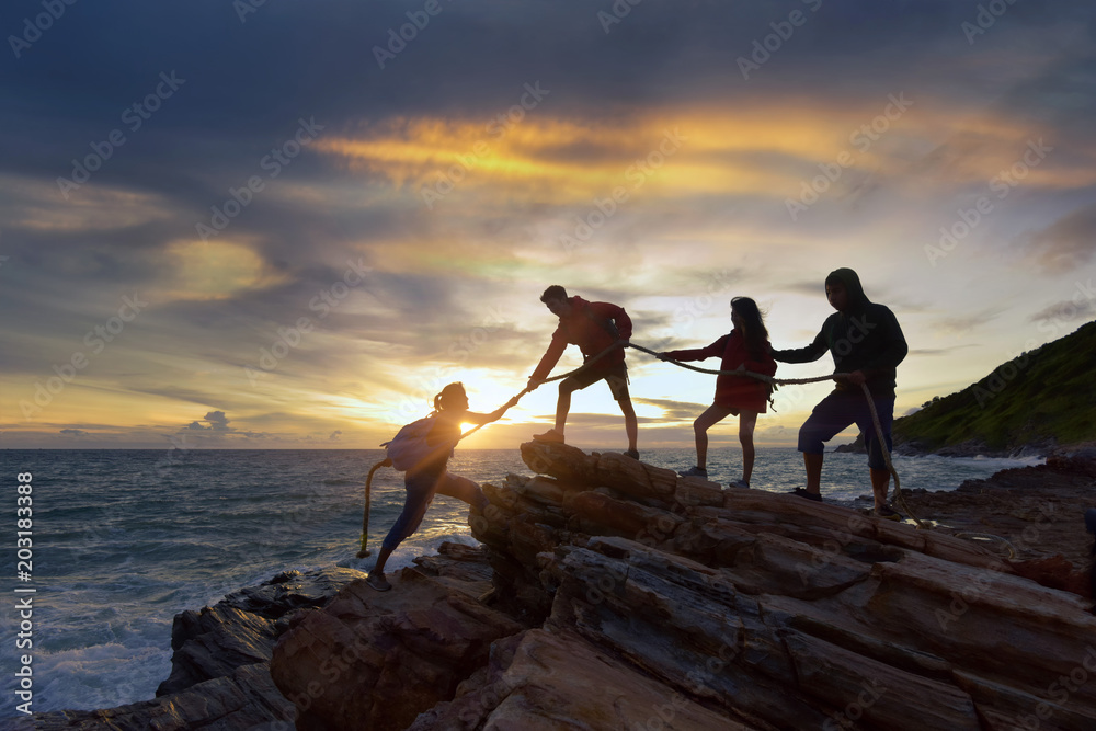Fototapety, obrazy:  silhouette male and female hikers climbing up  mountain cliff . helps and team work concept.