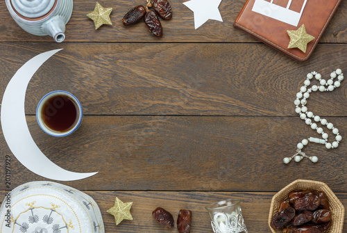 Table top view aerial image of decoration Ramadan Kareem holiday background.Flat lay date in wood basket with white rosary & decor.Objects on modern rustic brown wood at office desk with copy space.