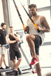 handsome sporty young man training with suspension straps in gym