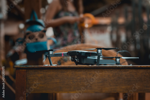 Fototapeta Modern professional quadro drone lies in the wooden table ready for use