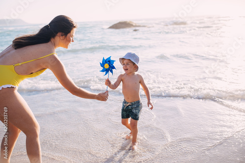 caucasian mother and sun playing with windmill at the beach