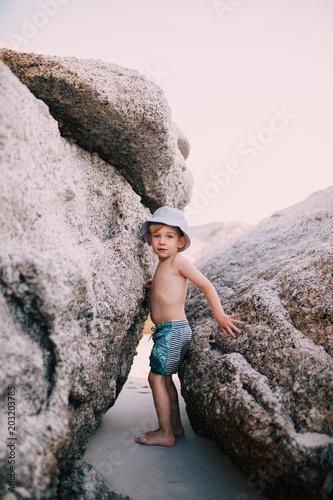 little caucasian boy climbing between big rocks at the beach