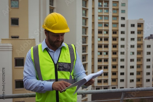 Architect checking documents on clipboard