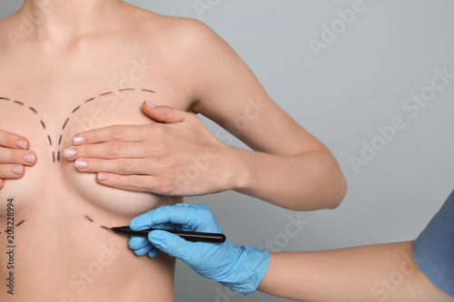 Doctor drawing marks on female breast for cosmetic surgery operation against col Fototapete