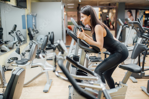 Foto op Plexiglas Fitness Aerobics spinning woman exercise workout at bikes gym, fit girl riding fitness bicycle at gym