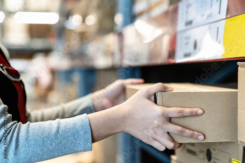 Foto Asian woman's hand shopping in self picking box,package and collect product from shelf,rack in warehouse,store