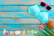 Summer background with bikini, sunglasses, coconut, starfish, coral and shells on blue wooden background. Summer concept, Vintage retro styles