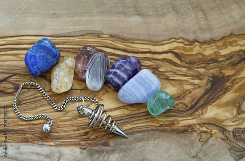 Healing Crystals and Dowsing Pendant - Selection of healing crystals and a spiral dowsing pendant arranged on a piece of flat smooth olive wood