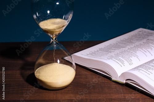 Hourglass and open Bible Fototapet