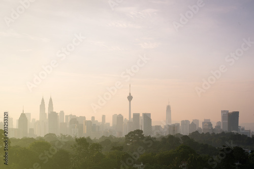 Photo  beautiful view of Kuala Lumpur city skyline in the early morning with haze or fog and building is semi silhouette
