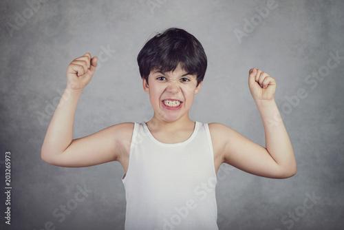 Photo  niño fuerte que enseña sus músculos sobre fondo gris