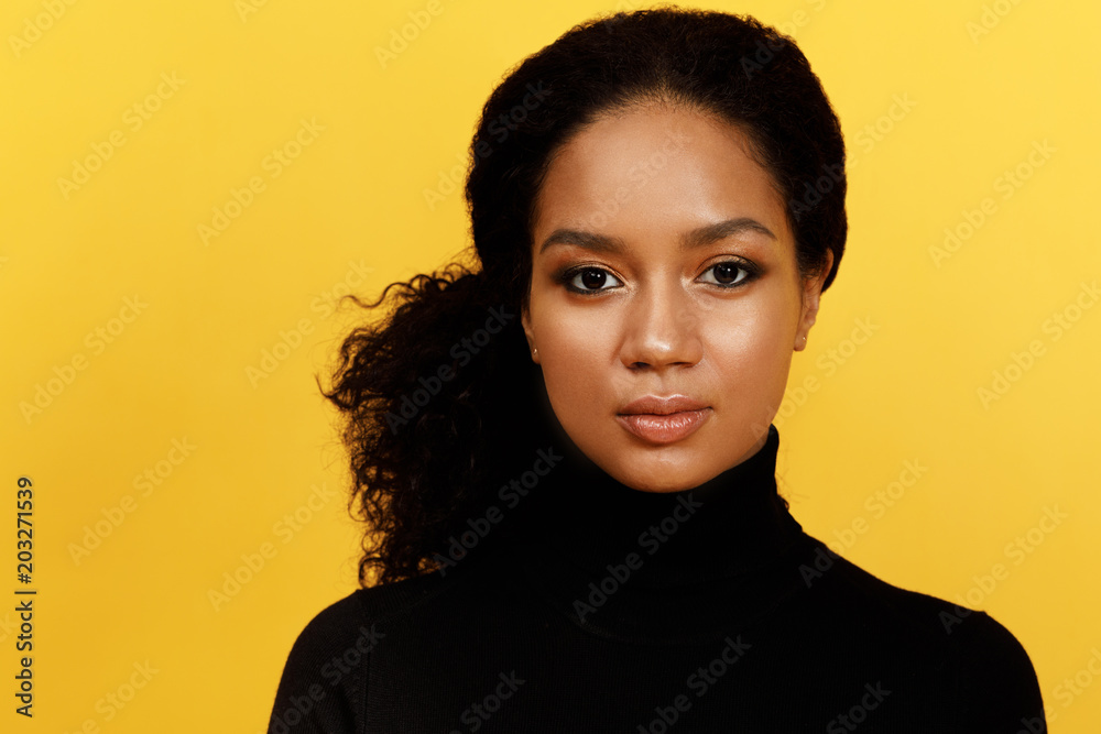 Fototapeta Portrait of a serious woman over yellow background
