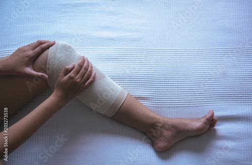 Woman Using Elastic Bandage With Legs Having Knee Or Leg Pain