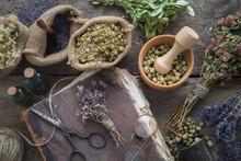 Old Book, Eyeglasses, Tincture Bottles, Assortment Of Dry Healthy Herbs, Mortar. Herbal Medicine. Top View, Flat Lay.