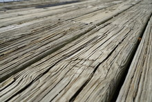Old Dark Rough Wood Floor Or Surface With Splinters And Knots. Horizontal Parallel Flooring Or Boards With Wood Grain. Old Aged Boardwalk Or Decking.