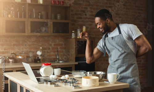 African-american man baking cookies at home kitchen