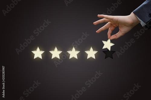Pinturas sobre lienzo  Hand of a businessman holding the fifth star.
