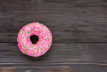 Pink Donut On Brown Wooden Background. Top View. Copy Space For Text, Logo And Design