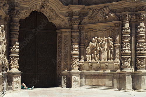 Photo Picture of the facade of a huge church with some statues of women talking and whispering each other and two manly legs in green shorts and sneakers