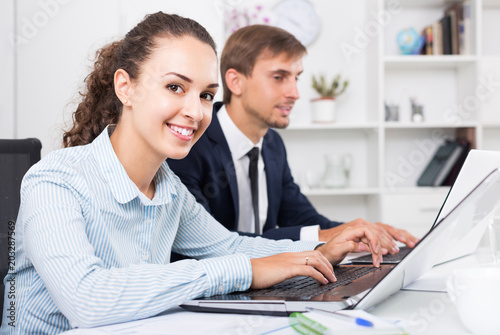Canvas-taulu portrait of  business woman sitting with laptop on desk in office on working day
