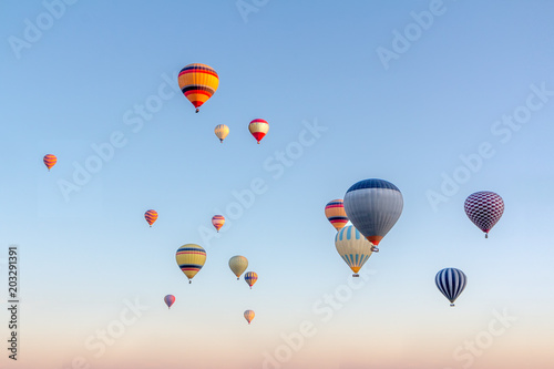 Bright multi-colored hot air balloons flying in sunsrise sky Cappadocia