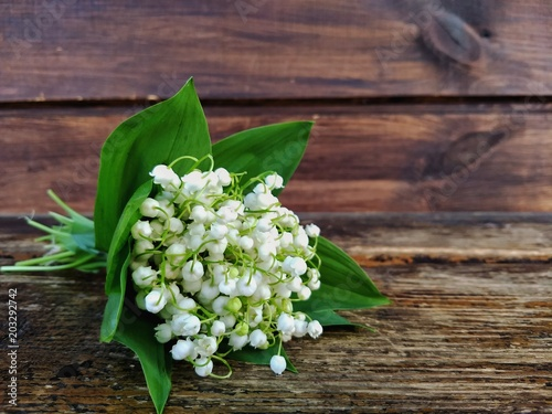 Wall Murals Bouquet of lily of the valley on a wooden background