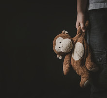 Boy Holding Stuffed Toy While Standing Against Black Background
