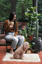 Young Woman Having Drink While Looking At Poodle By Potted Plants On Porch