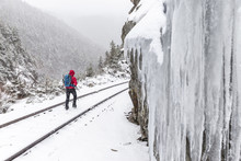 Rear View Of Woman Walking On Snow Covered Railroad Track