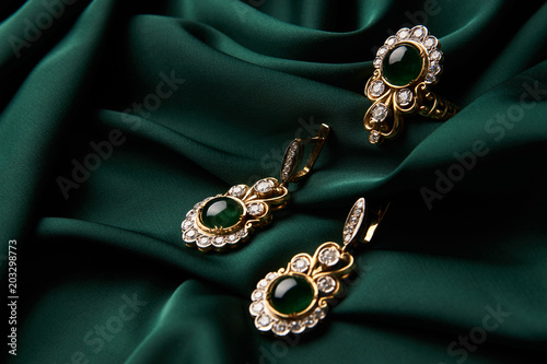 Beautiful Golden ring and pair of earrings with green Emerald and Diamonds gemstones on a green satin background. Luxury female jewelry, close-up. Selective focus