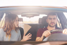 Terrified Female Gestures Actively And Tells Something Emotionally To Her Husband Who Drives Car And Tries Not Distract From Road, Have Long Trip In New Automobile. People, Family, Trip Concept