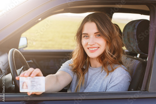Fotografía  Smiling young female with pleasant appearance shows proudly her drivers license, sits in new car, being young inexperienced driver, looks with joyful expression
