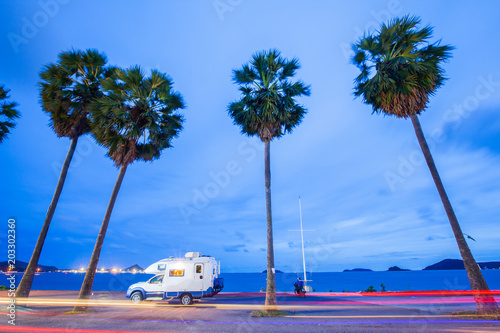Photo  Traveling by campervan or motorhome on road along the sea at sunset