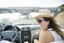 Happy Woman Wearing Hat While Traveling In Convertible Against Sky