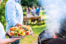 In Summer. A Couple Prepares A Bbq To Welcome Friends In The Garden. Close-up On A Plate Of Grill Skewers
