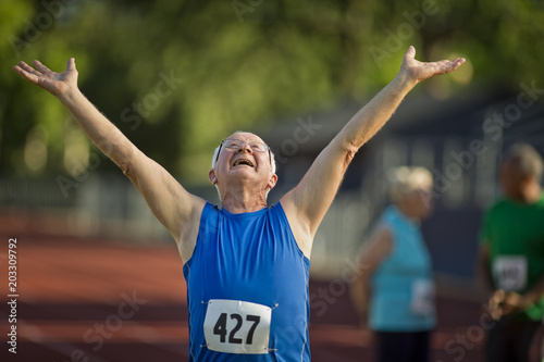 Happy senior man cheering after finishing a competitive running race.