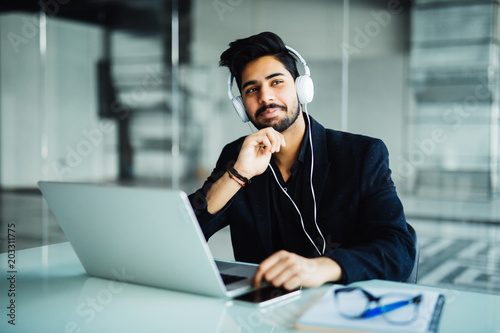 Fototapety, obrazy: Young businessman working with laptop computer and headphone in the office