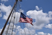 American Flag With 15 Stars Waving From Tall Ship Mast, Blue Sky With Clouds.