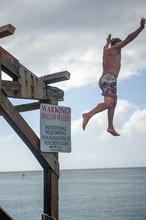 Man Jumping Off Hanalei Pier Hanalei Bay Kauai Hawaii