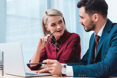 yiung businesswoman holding eyeglasses and flirting with handsome male colleague Tablou Canvas